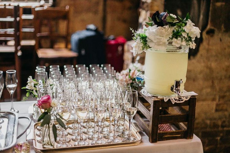 Drinks table at colourful and fun reception in London with floral and pine cone wedding decor