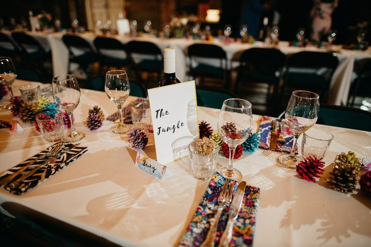 Reception styling for colourful, fun and eclectic day with pine cone wedding decor and hand painted placecards