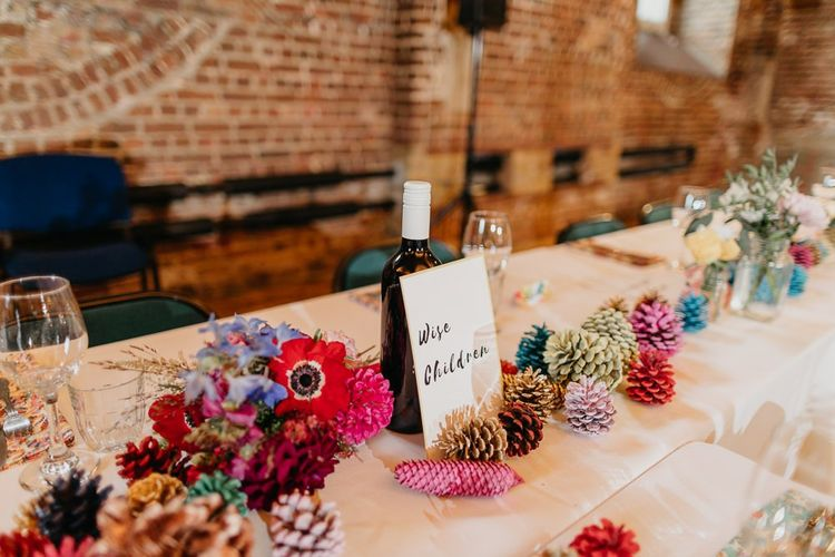 Styling for colourful and eclectic day with pine cone wedding decor and bright floral centrepieces