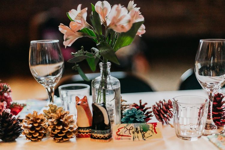 Centrepieces with pine cone wedding decor bright floral arrangements and ceramic animals