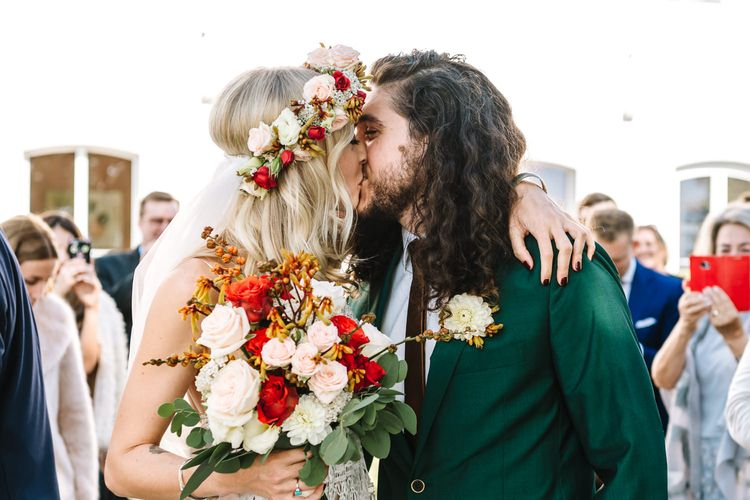 Boho Bride in Red and White Flower Crown Kissing Groom in Green Wedding Suit