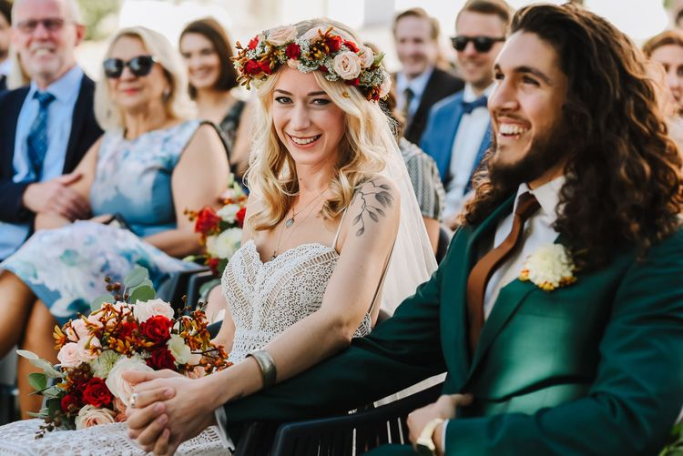 Wedding Ceremony with Boho Bride in Red and White Flower Crown Holding Hands with Groom in Green Wedding Suit