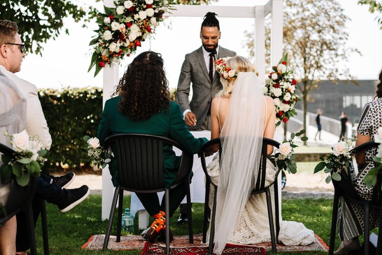 Wedding Ceremony with Bride in Red and White Flower Crown and Groom in Green Wedding Suit Sitting in Front of Flower Arch