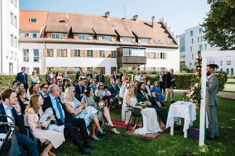 Outdoor Wedding Ceremony in Austria with Bride Wearing Flower Crown and Groom in Green Wedding Suit