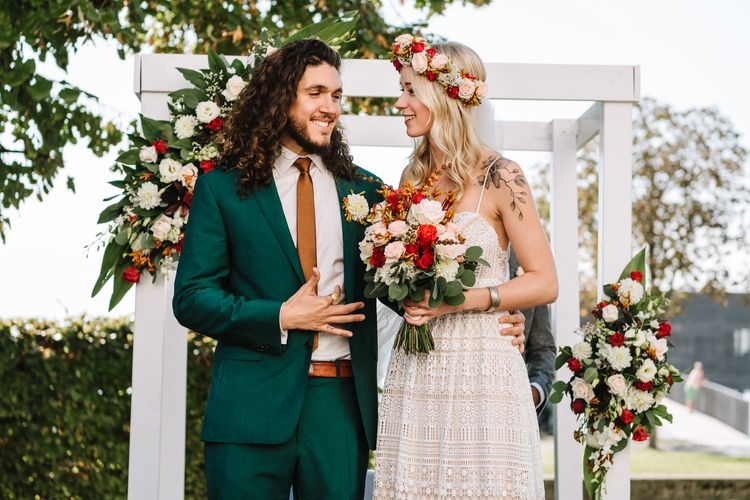 Bride in Red and White Flower Crown and Groom in Green Wedding Suit Standing in Front of Flower Covered Altar