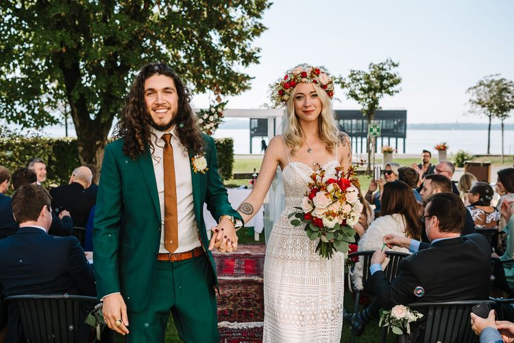 Bride in Lace Lillian West Wedding Dress and Groom in Green Wedding Suit with Red, White and Foliage Wedding Flowers
