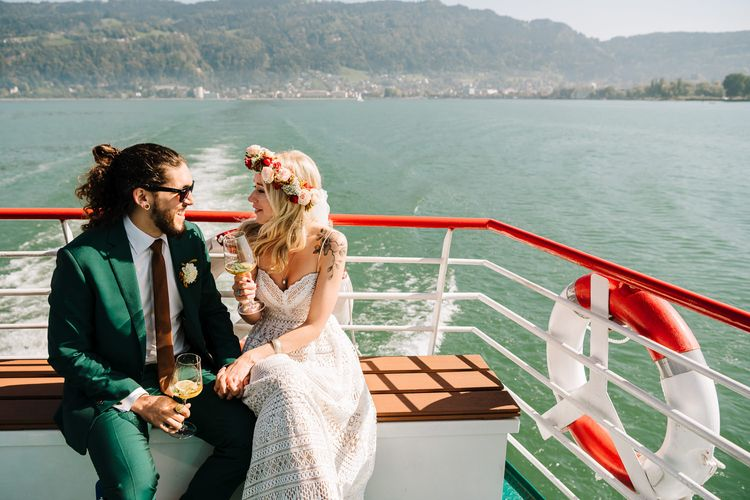 Boho Bride in Lace Lillian West Wedding Dress and Flower Crown and Groom in Green Wedding Suit Enjoying Boat Ride on Lake Constance