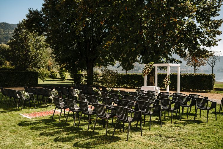 Outdoor Wedding Ceremony Setup with White Framed Altar Covered in Flowers