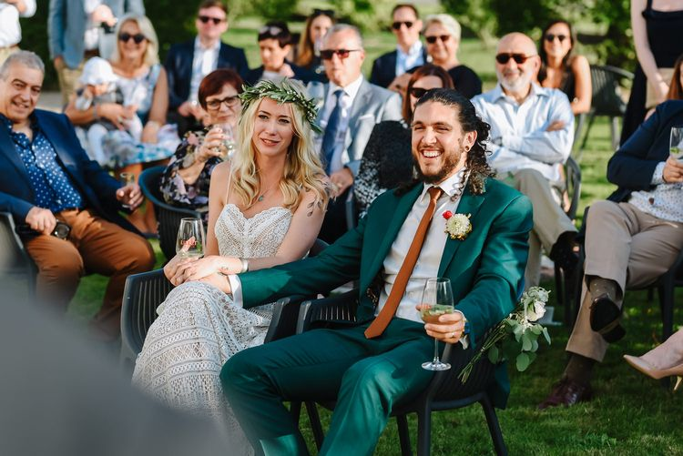 Bride in Lace Lillian West Wedding Dress and Groom in Green Wedding Suit Laughing During Outdoor Wedding Speeches