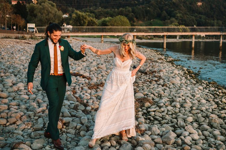 Boho Bride in Lillian West Wedding Dress and Groom in Green Wedding Suit Standing on the Shores of Lake Constance