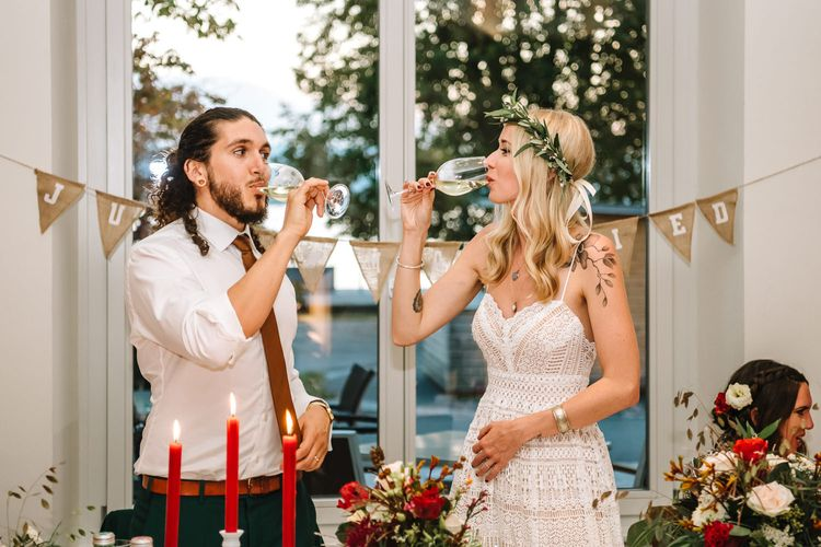 Bride and Groom Drinking a Toast at the Wedding Reception with Burlap Bunting Backdrop