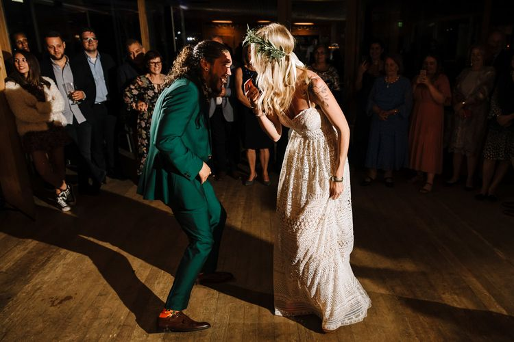 Bride in Lillian West Wedding Dress and Groom in Green Wedding Suit Enjoying First Wedding Dance
