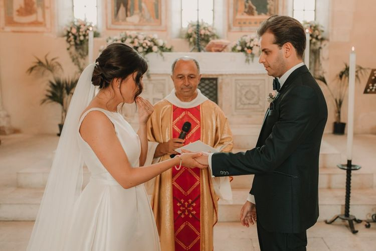Bride in Rosa Clara wedding dress with veil during church ceremony