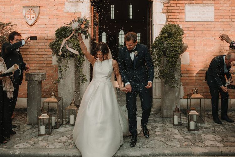 Confetti exit for bride in Rosa Clara wedding dress and groom