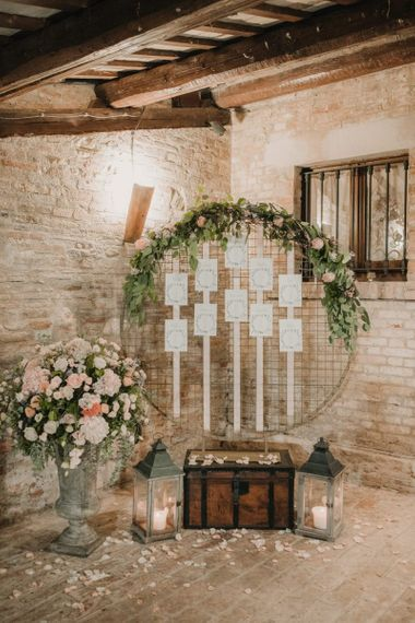 Rustic hoop wedding seating chart with foliage and flower decor
