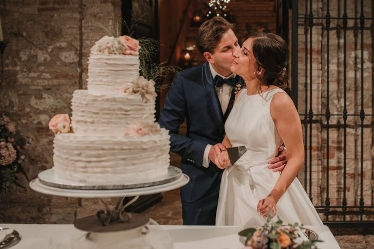 Large white wedding cake with bride in Rosa Clara dress and groom