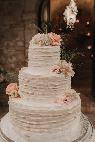 White wedding cake with pink flower decor
