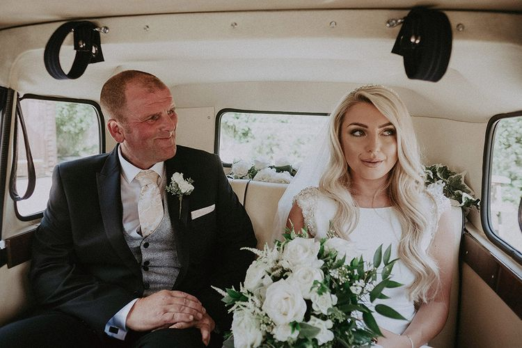 Father of the Bride and Bride in St Patrick Wedding Dress Sitting in Vintage Wedding Car