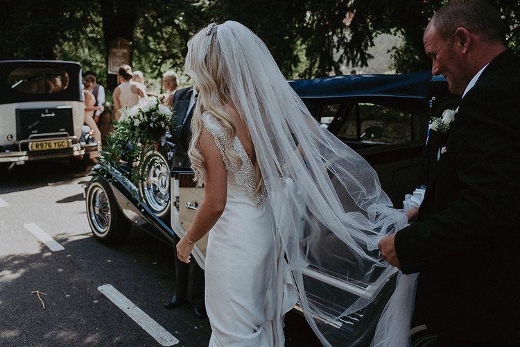Bridal Entrance in Vintage Wedding Car Wearing St Patrick Wedding Dress and Wedding Veil