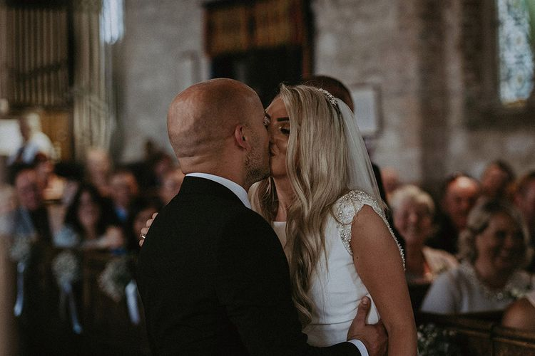 Church Wedding Ceremony with Bride in St Patrick Wedding Dress and Groom in Dark Suit Kissing