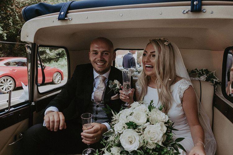 Bride in St Patrick Wedding Dress and Groom in Dark Suit Sitting in Classic Wedding Car