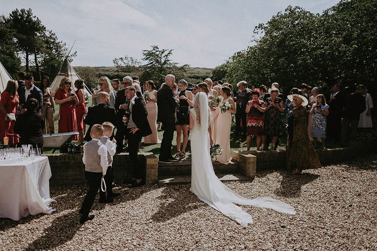 Bride in St Patrick Wedding Dress and Cathedral Veil Enjoying Drinks Reception at East Afton Farmhouse