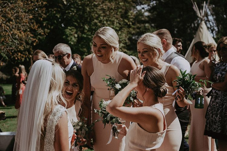 Bride and Bridesmaids Laughing During Drinks Reception