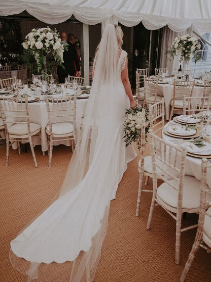 Bride in St Patrick Wedding Dress and Cathedral Length Veil Walking Through Marquee Wedding Reception