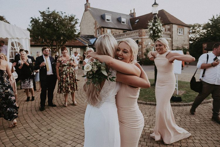 Bride and Bridesmaid Hugging After the Wedding Bouquet Toss