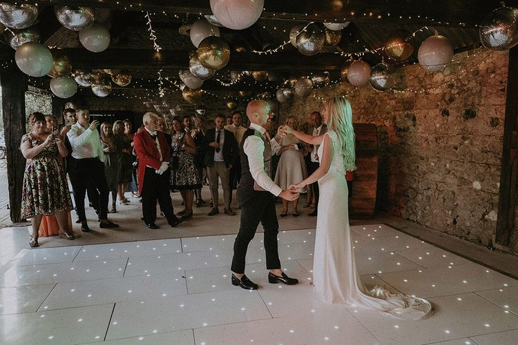 Bride and Groom First Dance with Fairy Lights and Balloons Decorating The Ceiling