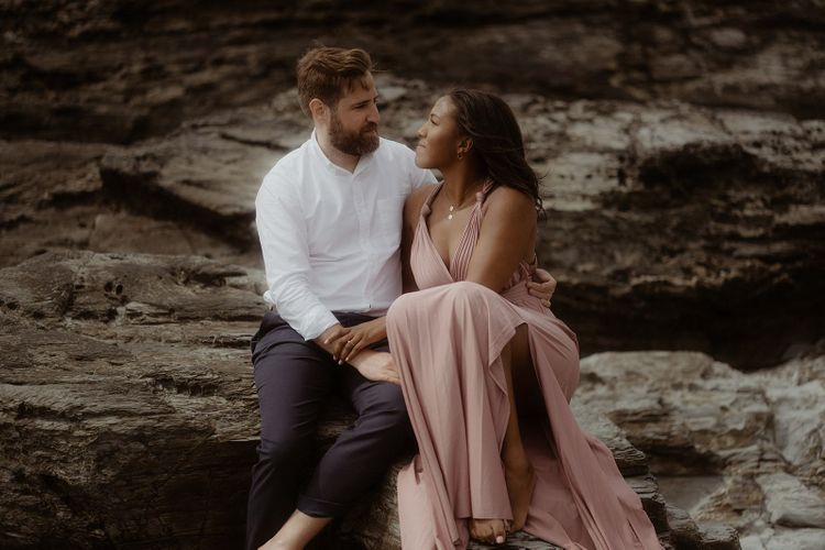 Bride and groom sitting on the rocks at their beach engagement session