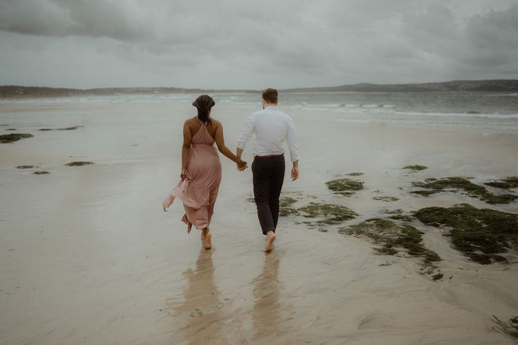 Bride and groom-to-be walking in the surf at Cornwall beach engagement session