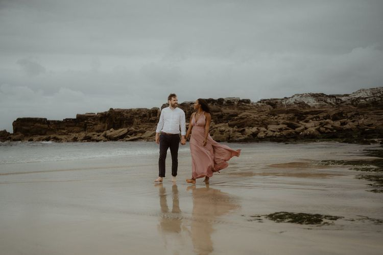 Bride and groom walking through the surf on the beach