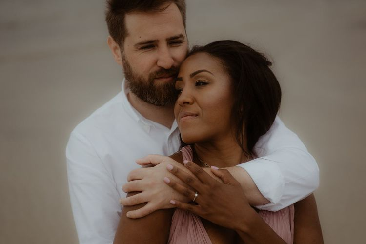 Groom in white shirt embracing his bride-to-be during their engagement session