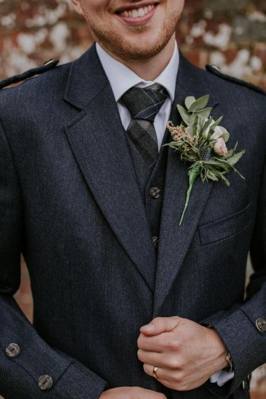 Groom in kilt with floral buttonhole and thistle