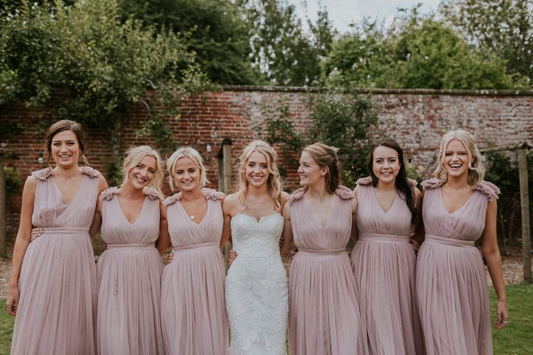 Pink bridesmaid dresses next to Enzoani wedding dress