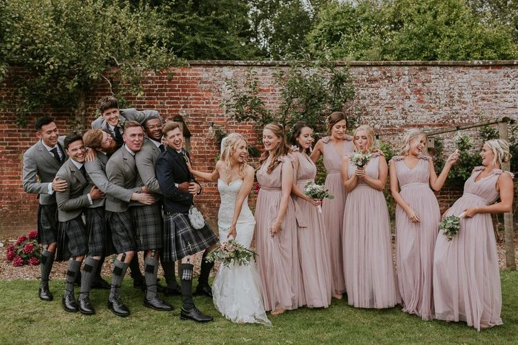 Pink bridesmaid dresses next to bride in Enzoani wedding dress