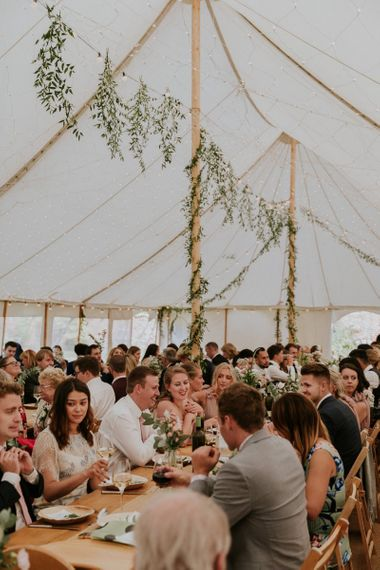 Guests enjoy dinner in marquee wedding