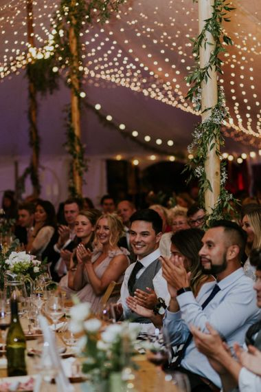 Guests enjoy wedding speeches with fairy lights in marquee