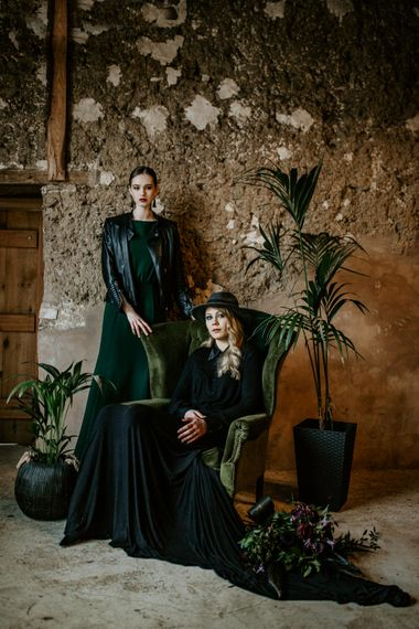 Green Velvet Chair | Botanical Plants | Bride in Black Dress & Leather Jacket | Bridesmaid in Forest Green Dress & Leather Jacket | Forest Green and Black Dark Decadence Wedding Inspiration in a Rustic Barn Planned & Styled by Knots & Kisses with Images by Daze of Glory Photography