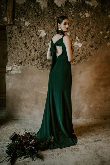 Bridesmaid in Tie Back Forest Green Dress | Forest Green and Black Dark Decadence Wedding Inspiration in a Rustic Barn Planned & Styled by Knots & Kisses with Images by Daze of Glory Photography
