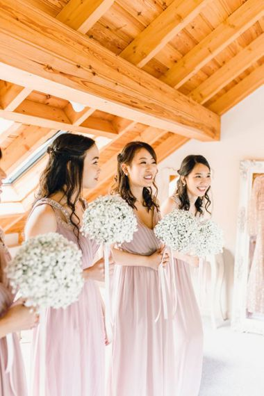 Bridesmaids in dusky pink dresses for traditional celebration with gypsophila bouquets