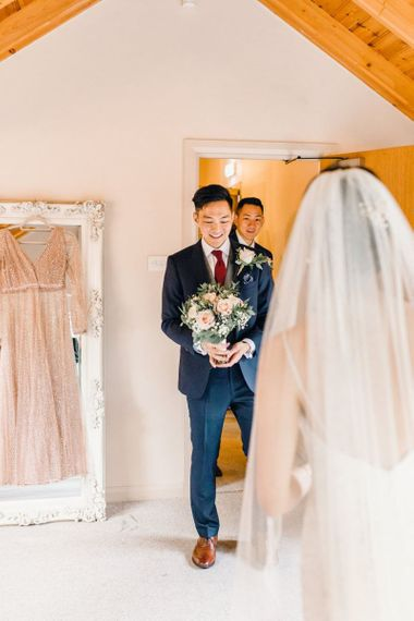 Groom seeing the bride before the ceremony with dusky pink rose bouquet