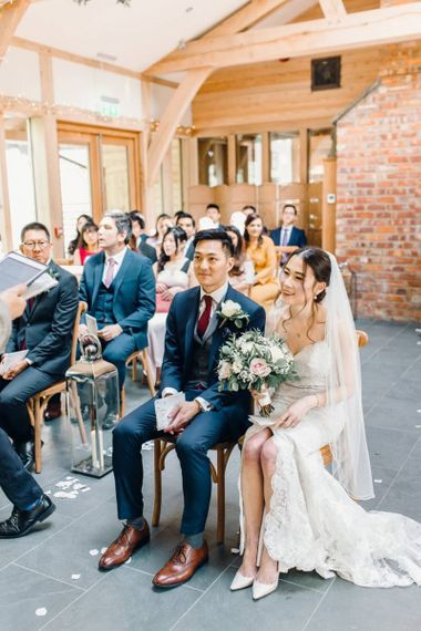 Bride and groom take a seat at this traditional ceremony with rustic detailing
