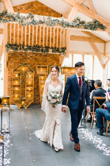 Bride and groom tie the knot with wooden Love sign decorated with green foliage and lanterns