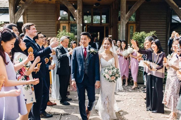 Bride wearing a lace dress and groom in a three piece suit leaving the wedding ceremony