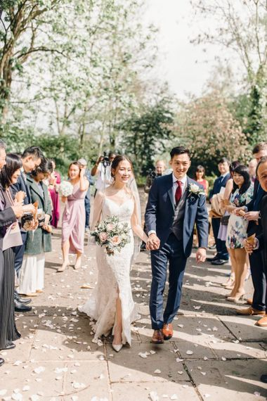Bride and groom confetti shot with dusky pink rose wedding bouquet