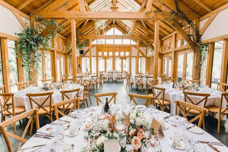 Rustic styled wedding reception with beams decorated in green foliage and gypsophila bouquets