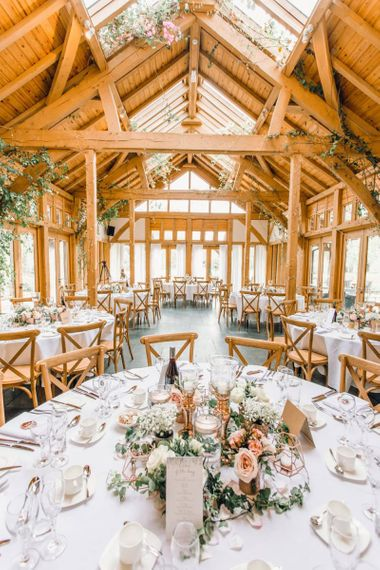 Rustic styled wedding reception with rose gold centrepiece decor and dusky pink roses