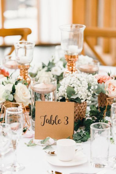 Table number signs with rose gold detailing and gypsophila bouquets